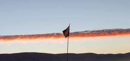 It was a beautiful dawn. This is the wiphala, one of the two official flags of Bolivia (and the traditional flag of native peoples of the Andes) against the sunrise.