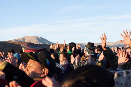 Everyone's hands in the air, celebrating the arrival of father sun and of the new year, 5521 by the traditional Aymara count.